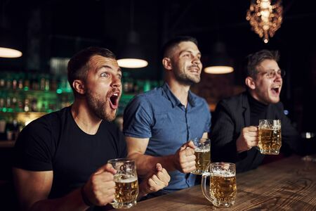 Photo for Celebrating victory. Three sports fans in a bar watching soccer. With beer in hands. - Royalty Free Image