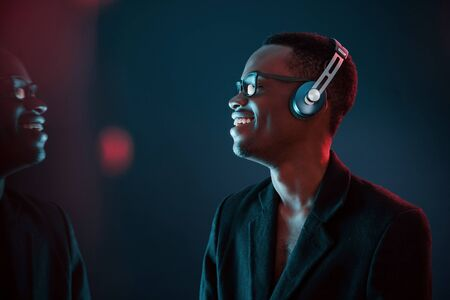 Photo pour Enjoying listening music in headphones. In glasses. Futuristic neon lighting. Young african american man in the studio. - image libre de droit