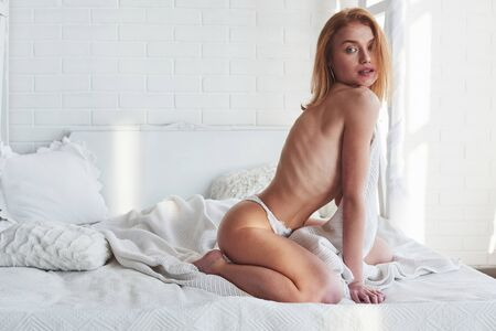 Photo pour Posing in the bedroom. Hot redhead girl sits on the white bed with no bra. Covering chest. - image libre de droit