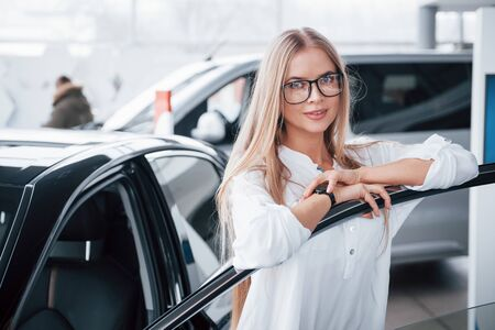 Photo for Cute girl in eyewear stands near the car in auto saloon. Probably her next purchase. - Royalty Free Image