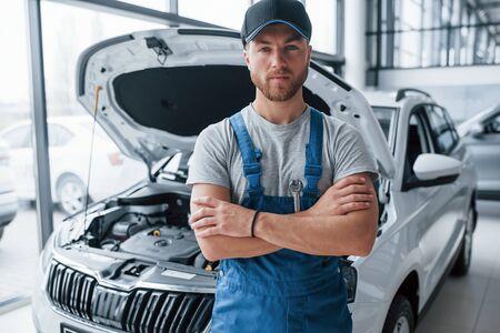 Photo pour Employee in the blue colored uniform stands in the automobile salon. - image libre de droit