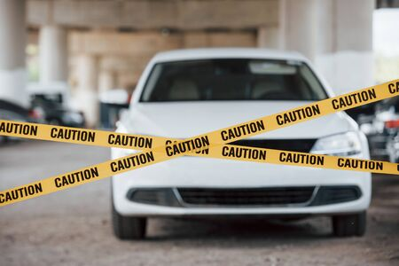 Photo for No trespass allowed here. Yellow caution tape near the car parking lot at daytime. Crime scene. - Royalty Free Image
