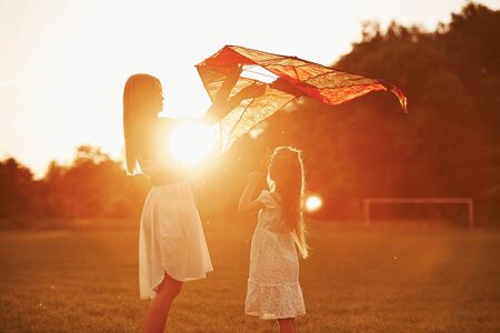 Photo for Orange colored sunset. Mother and daughter have fun with kite in the field. Beautiful nature. - Royalty Free Image