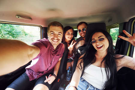 Photo for Young and cheerful people making a selfie inside a car. Having weekend. - Royalty Free Image