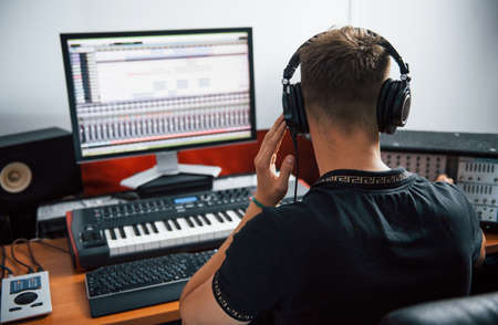 Photo pour Sound engineer in headphones working and mixing music indoors in the studio. - image libre de droit