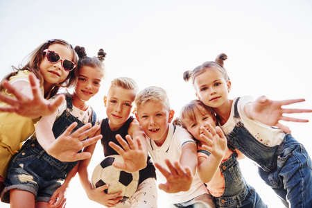 Photo for Hello, gesture. With soccer ball. Portrait of kids that standing together and posing for the camera. - Royalty Free Image