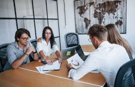 Photo pour Some documents on the table and in hands. Young business people in formal clothes working in the office. - image libre de droit