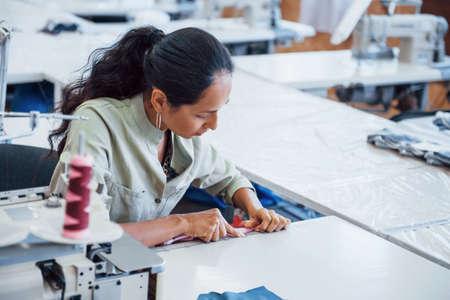 Photo pour Dressmaker woman sews clothes on sewing machine in factory. - image libre de droit