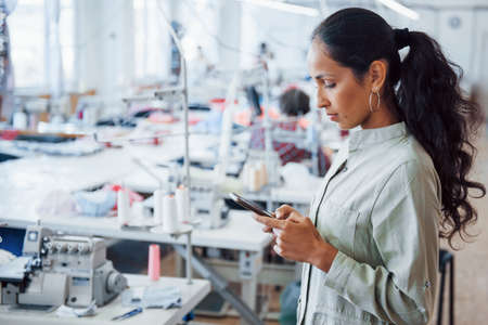 Photo pour Woman dressmaker stands in the factory with phone in hands. - image libre de droit