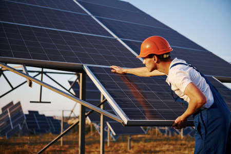 Photo for Manual work. Male worker in blue uniform outdoors with solar batteries at sunny day. - Royalty Free Image