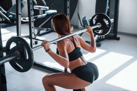 Photo for Young fitness woman with slim type of body doing exercises by using barbell. - Royalty Free Image
