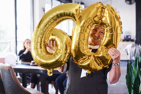 Photo pour With balloons of number 60 in hands. Senior woman with family and friends celebrating a birthday indoors. - image libre de droit