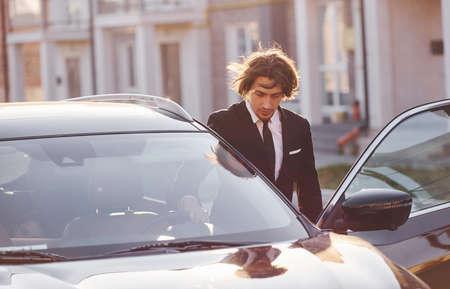 Photo pour Portrait of handsome young businessman in black suit and tie outdoors near modern car in the city. - image libre de droit