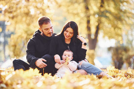 Photo pour Cheerful family sits on the ground and having fun together with their child in beautiful autumn park. - image libre de droit