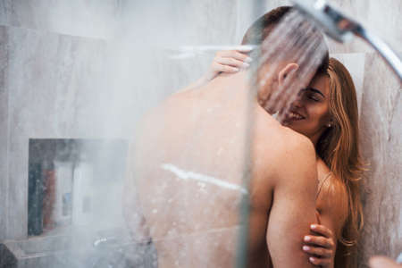 Photo for View through the glass of young couple that embracing and kissing each other in the bathroom. - Royalty Free Image