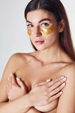Photo pour Naked woman is in the studio against white background with golden tapes near eyes. - image libre de droit