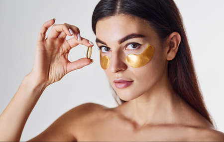 Photo pour Naked woman in the studio with golden tapes near eyes and with pill in hand. - image libre de droit