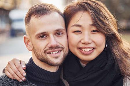 Photo pour Portrait of multiracial couple. Asian girl with her caucasian boyfriend. - image libre de droit