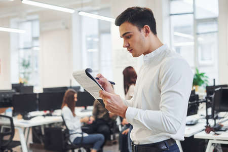 Photo pour Man in formal wear standing with notepad in hands indoors in office with young people that works behind him. - image libre de droit