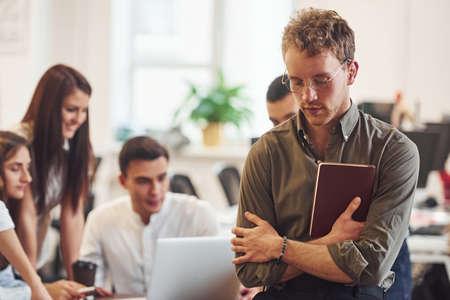 Foto de Man in glasses standing in front of his colleagues in the office. - Imagen libre de derechos