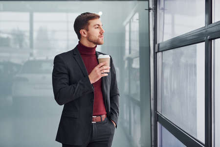 Photo pour Young business man in luxury suit and formal clothes wth cup of drink is indoors in the office. - image libre de droit