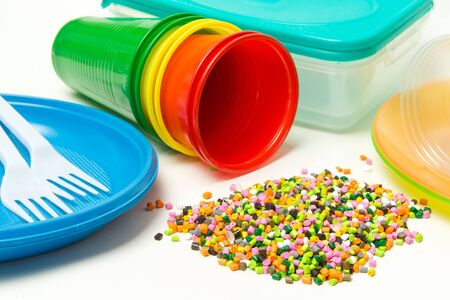 Photo pour Plastic granules and disposable tableware made of polyethylene, polypropylene polymeric material on a white background. BPA FREE - image libre de droit