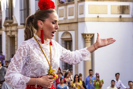 CORDOBA, SPAIN - MAY 30, 2019: Female flamenco singer sings in front of the Mosque-Cathedral at Feria de Cordoba, Feria de Nuestra Senora de la Salud or Cordoba Fair
