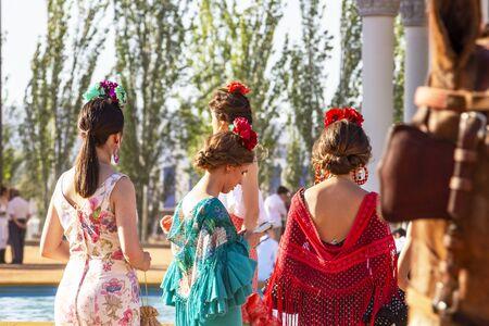 CORDOBA, SPAIN - MAY 30, 2019: Rear view of beautiful dressed female participants at Feria de Cordoba, Feria de Nuestra Senora de la Salud or Cordoba Fair