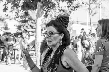 CORDOBA, SPAIN - MAY 30, 2019: Close portrait of a senior dressed female participant at Feria de Cordoba, Feria de Nuestra Senora de la Salud or Cordoba Fair with a hand fan