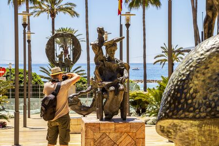 MARBELLA, SPAIN - MAY 26, 2019: Male photographer takes picture of Don Quijote Sentado or Don Quixote Sitting sculpture by Salvador Dali of Avenida del Mar