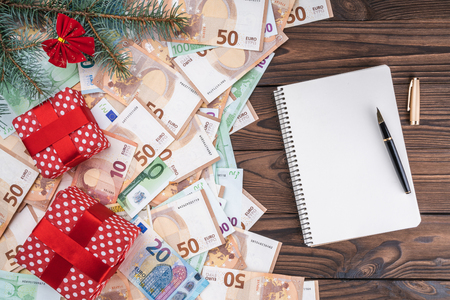 Photo pour European money of different value on wood background. Gifts under fir branches. Space for text. Top view. - image libre de droit