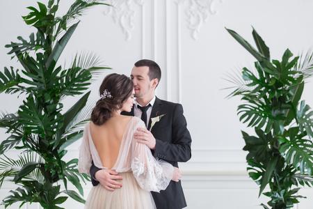 Foto de Beautiful brunette bride and groom portrait, back view, close up of gorgeous newlywed woman in stylish beige wedding dress with open back, rear view - Imagen libre de derechos