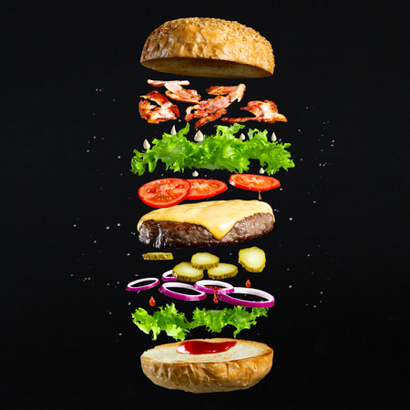 Foto de Floating burger isolated on black wooden background. Ingredients of a delicious burger with ground beef patty, lettuce, bacon, onions, tomatoes and cucumbers - Imagen libre de derechos