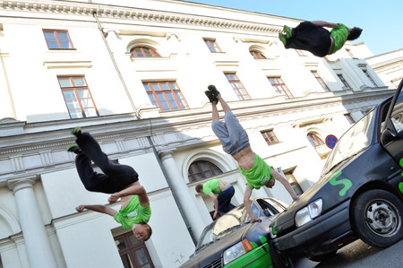 Warsaw, Poland - September 17, 2011:  Parkour acrobats jumping over the cars at the street of Warsaw.