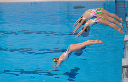 Warsaw, Poland - June 12, 2011: A synchronized swimming team, jumps into the water, during the competition at the University of Physical Education.