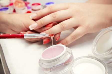 Artificial nails in a beauty salon  Hands close-up  The process of nails