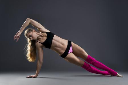 Foto de Beautiful muscular woman doing exercise side plank on a gray background in studio - Imagen libre de derechos