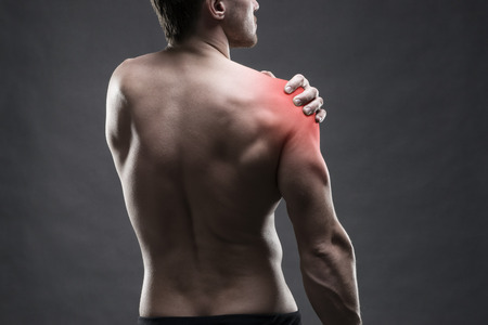 Photo pour Pain in the shoulder. Muscular male body. Handsome bodybuilder posing on gray background with red dot - image libre de droit