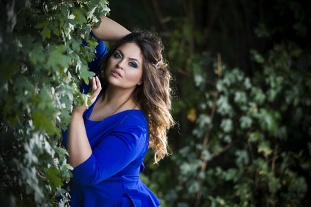 Photo pour Young beautiful caucasian plus size model in blue dress outdoors, xxl woman on nature, professional makeup and hairstyle - image libre de droit
