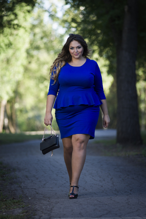 Young beautiful caucasian plus size fashion model in blue dress outdoors, xxl woman on nature, full length portraitの写真素材
