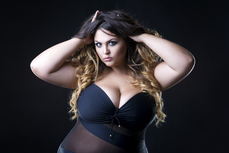 Photo pour Young beautiful plus size model in underwear, xxl woman on black background, professional makeup and hairstyle - image libre de droit