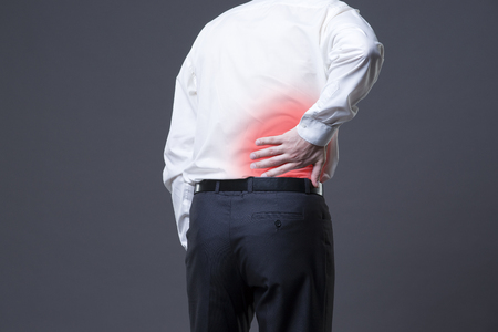 Back pain, kidney inflammation, ache in man\'s body on gray background with red dot
