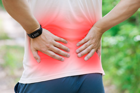 Man with back pain, kidney inflammation, trauma during workout, outdoors concept