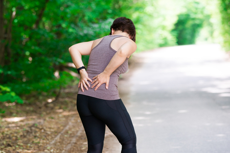 Woman with back pain, kidney inflammation, injury during workout, outdoors concept