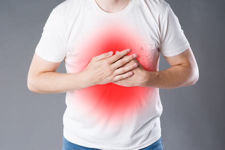 Heart attack, man with chest pain on gray background, painful area highlighted in red