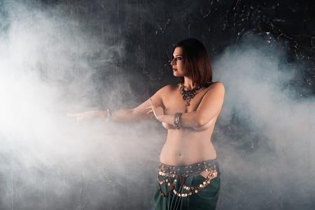 Foto de Sexy women performs belly dance in ethnic dress on dark smoky background, studio shot - Imagen libre de derechos