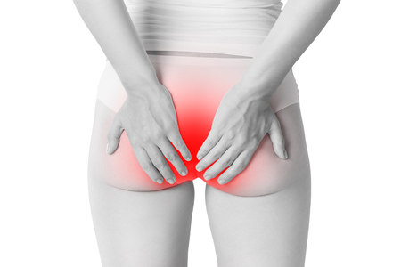 Foto de Woman suffering from hemorrhoids, anal pain isolated on white background, painful area highlighted in red - Imagen libre de derechos
