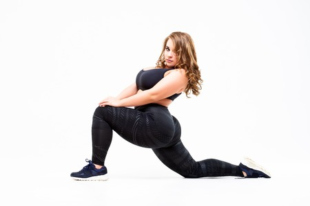 Foto de Plus size model in sportswear, fat woman doing workout on white studio background, body positive concept - Imagen libre de derechos