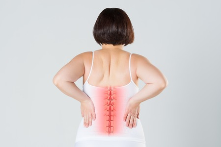 Photo pour Pain in the spine, a woman with backache, injury in the human back, chiropractic treatments concept with highlighted skeleton - image libre de droit