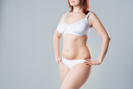 Photo pour Woman with fat flabby belly, overweight female body on gray background, studio shot - image libre de droit